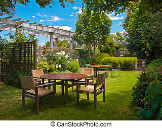 dining table set in lush garden - a wooden dining table set...