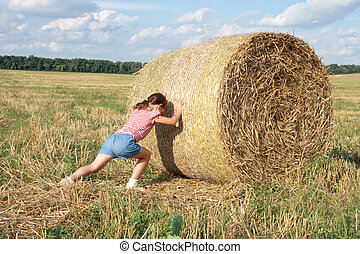 bale of hay - child pushes a bale of hay