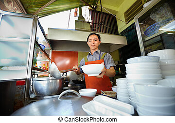 Man working as cook in Asian restaurant kitchen - Chef...