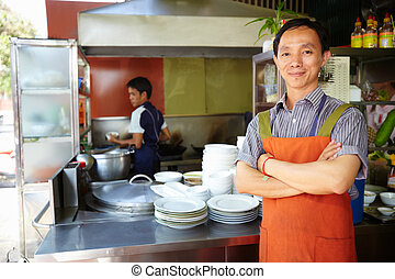 Man working as cook in Asian restaurant kitchen - Portrait...