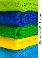 Colour terry towels combined by pile on white background...