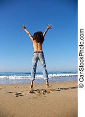 back of woman jumping at seashore - woman back at Arenal...