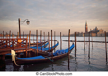 Gondolas in Venice - Gondolas moored at a getty at sunset in...