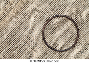Metal ring on burlap fabric