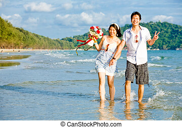 portrait of couples walking by hand in hand along the beach with gentle ripple