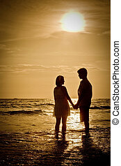 romantic Scene of couples on the Beach with sunset