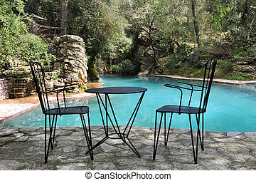 chairs and table on terrace near a natural swimming pool