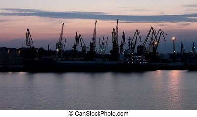 Silhouette of several cranes in a harbor, shot during sunset...