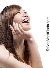 Laughing Asian woman looking up on white background