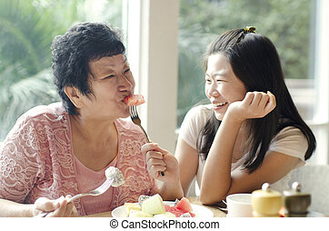 Healthy Ageing - Asian adult daughter feeding fruit to...