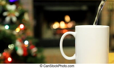 Christmas Drink - White mug sits in front of a burning...