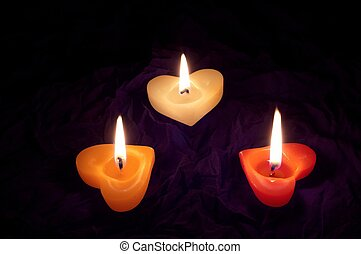 Coloured candle shaped heart on black backcloth