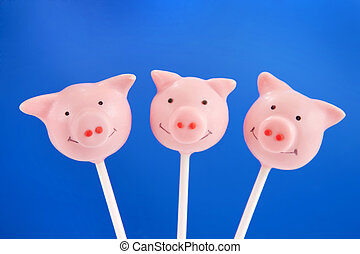 Pig cake pops - Tree pig pop cakes against blue background