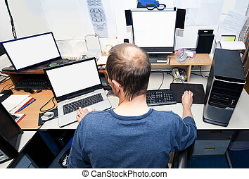 Computer technician - Man behind a desk with several...