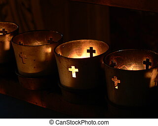 votive candles - Votive candles burning in a darkened...