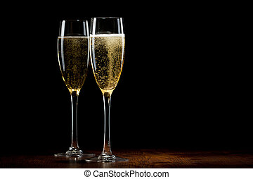 two glass with a champagne on a wooden table - two glass...