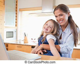 Happy mother and her daughter using a laptop in their...