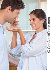Portrait of a man tasting his wife's sauce