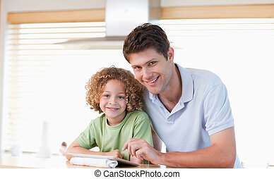 Smiling boy and his father using a tablet computer in their...