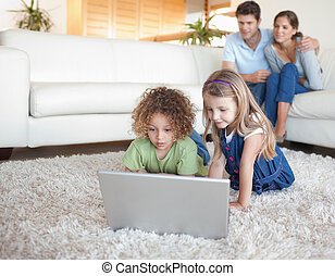 Children using a notebook while their parents are watching...