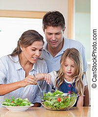 Portrait of a family preparing a salad in their kitchen