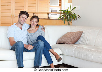Couple sitting on a sofa while looking at the camera