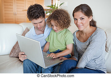Young family using a laptop in their living room