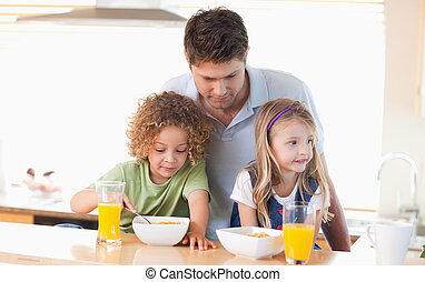 Young father with his children having breakfast