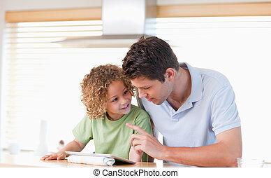 Young boy and his father using a tablet computer in their...