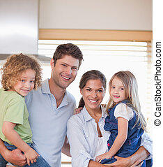 Smiling family standing up in their kitchen
