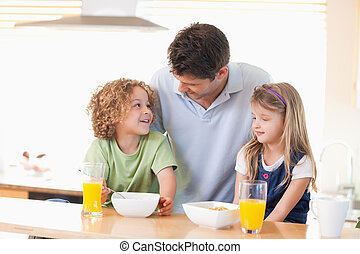 Smiling father with his children having breakfast in their...