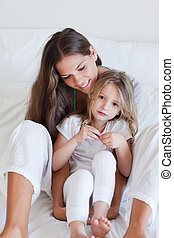 Portrait of a mother and her daughter posing on a bed...