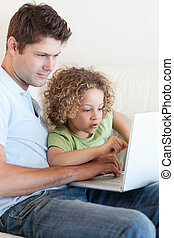 Portrait of a young boy and his father using a laptop in...