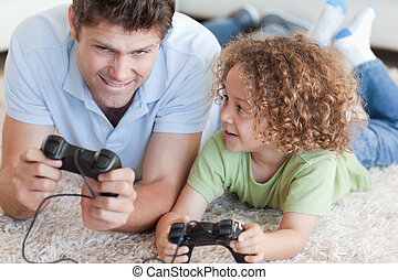 Boy and his father playing video games while lying on a...