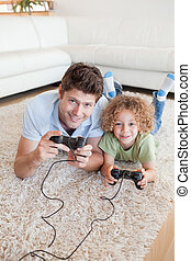 Portrait of a boy and his father playing video games while...