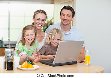 Smiling family using the internet in the kitchen - Smiling...