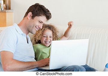 Cheerful boy and his father using a laptop in their living...