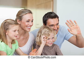 Family waving their hands in the kitchen