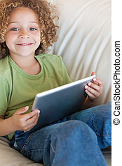 Portrait of a boy using a tablet computer in a living room