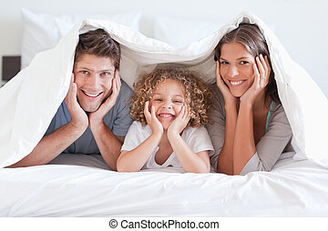 Happy family posing under a duvet while looking at the...