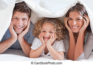 Family posing under a duvet while looking at the camera