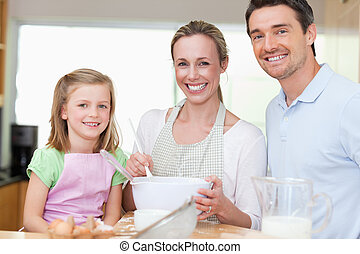 Girl preparing dough with her parents