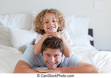 Child lying on fathers back in bed