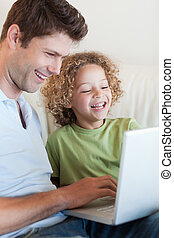 Portrait of a cute boy and his father using a laptop in...