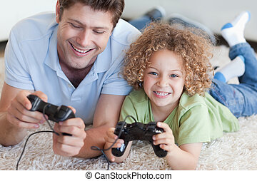 Happy boy and his father playing video games