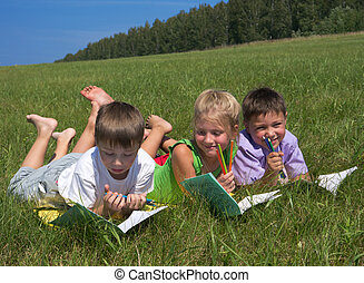 schoolkids - three schoolkids at meadow writing in notebooks