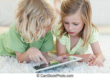 Siblings on the floor using tablet - Siblings together on...