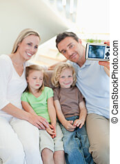 Man taking family picture on sofa