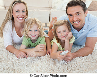 Family watching tv on the floor - Family watching tv...