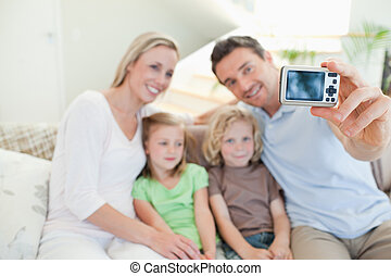 Father taking family picture on couch